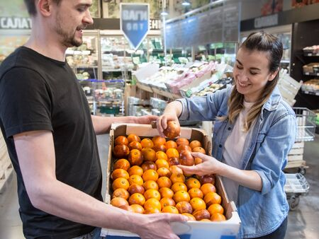 Smiling customers buying sicilian oranges, lemons and tangerines in grocery section Reklamní fotografie