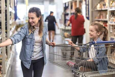 Mother and daughter in blue shirts shopping in supermarket using cart 写真素材