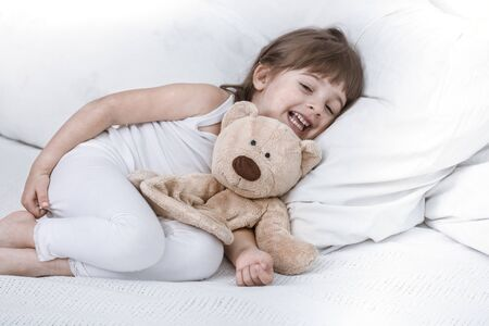Cute little girl smiling while lying in a cozy white bed with , the concept of children's rest and sleep Foto de archivo