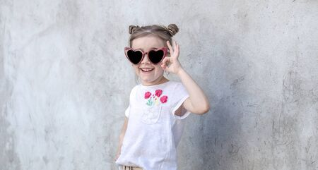 Outdoor portrait little girls with sunglasses. Gray textured wall background, copy space. Фото со стока