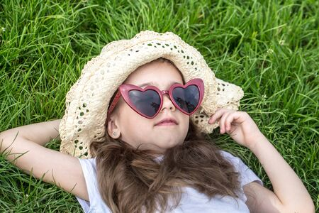 little girl laying in the grass with sunglasses and summer hat. summer time and sunny day