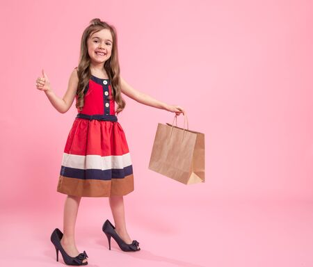 Little girl is a fashionista in dress and moms shoes with a shopping bag , colored pink background , Studio shot , concept of childrens fashion