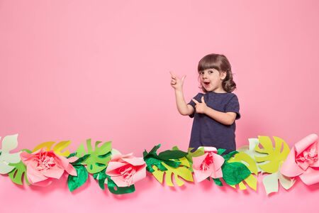 Portrait of a little girl on a summer pink background with paper flowers, place for text, summer advertising concept