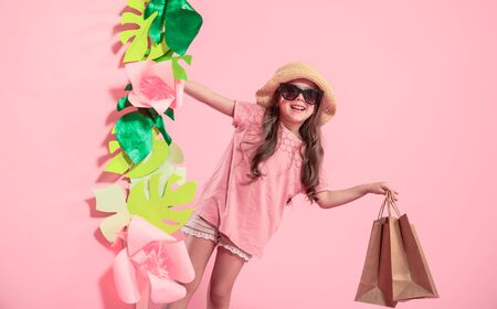 Portrait of cute little girl in glasses and summer hat , with shopping bag in hand on pink background with paper flowers, place for text, summer advertising concept Stock Photo