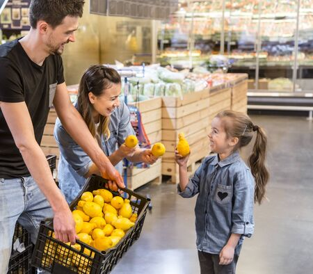 mother, husband and daughter choosing lemons in supermarket Reklamní fotografie