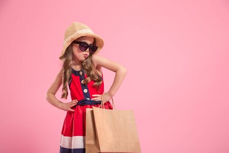 little fashionista with a shopping bag in summer hat and sunglasses , colorful pink background , the concept of childrens fashion Reklamní fotografie