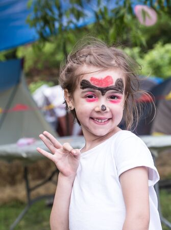 smiling girl with face art painting like tiger, little boy making face painting, halloween party, child with funny face painting, little cute boy with faceart on birthday party close up