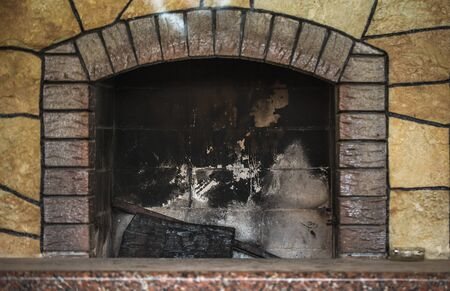 Red brick dirty fireplace with remains of ash after wooden firewood burnt in fireplace as advertising photo for companies serving and cleaning fireplaces Stock Photo