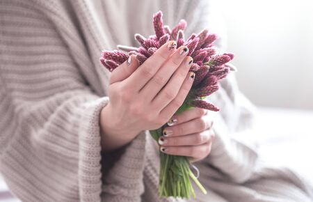 Close up of beautiful female hands holding big white cup of cappuccino coffee and flowers. Woman wearing warm winter knitted red sweater. Toned.