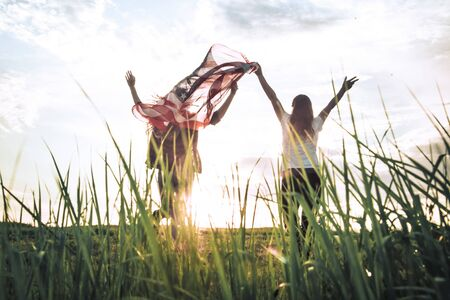Young happy girl running and jumping carefree with open arms over wheat field. Holding USA flag. Toned image. Selective focus.