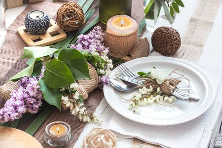 Beautifully elegant decorated table for holiday with spring flowers and greens - wedding or valentine day with modern cutlery, bow, glass, candle and gift, horizontal, closeup, toned