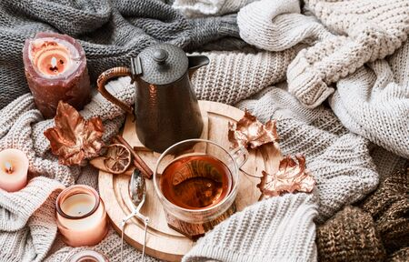 Cozy autumn morning breakfast in bed still life scene. Steaming cup of hot coffee, tea standing near window. Fall, Thanksgiving concept. White pumpkins, pine cones and oak leaves on wool plaid.