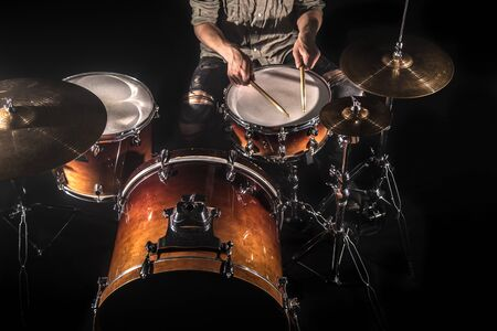 Professional drummer playing on drum set on stage on the black background with drum sticks and vintage look. Top view. Smoke effect 스톡 콘텐츠