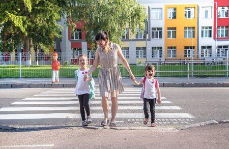 Zurück zum Schulbildungskonzept mit Mädchenkindern, Grundschülern, die am ersten Schultag Rucksäcke tragen, die Hand in Hand halten und glücklich die Gebäudetreppe hinaufgehen