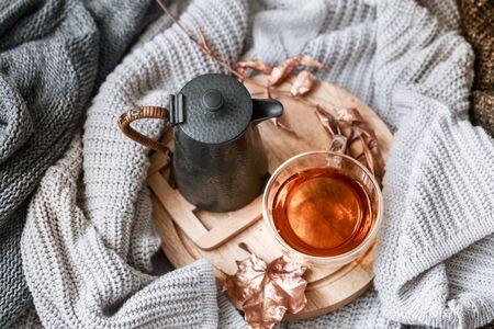 Gemütliches Herbstmorgenfrühstück in der Bettstilllebenszene Dampfende Tasse heißen Kaffee, Tee in der Nähe des Fensters. Herbst, Thanksgiving-Konzept. Weiße Kürbisse, Tannenzapfen und Eichenblätter auf Wollplaid. Standard-Bild