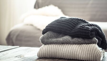 A stack of knitted sweaters on a wooden table, in the interior of the living room. The concept of autumn comfort