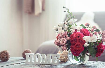 Stillleben mit Inschrift Haus und Vase mit Blumen verschiedener Rosen. Das Konzept des Wohnkomforts und der Einrichtung.