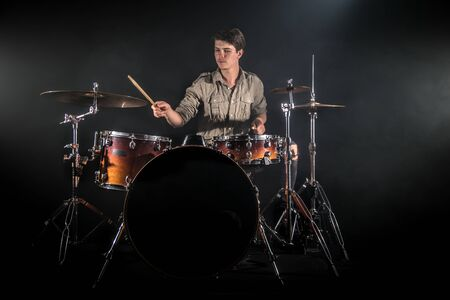 Professional drummer playing on drum set on stage on the black background with drum sticks and vintage look. Top view. Smoke effect