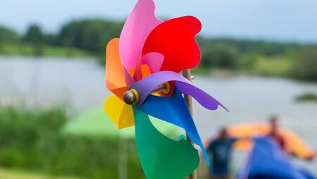 A child's pinwheel against a blue sky. Shot outside with studio lighting - not a composite.