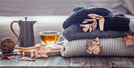 Accogliente natura morta autunnale con una tazza di tè e oggetti di arredo nel soggiorno. Concetto di comfort domestico Archivio Fotografico