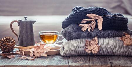 Acogedor bodegón otoñal con una taza de té y elementos de decoración en la sala de estar. Concepto de confort en el hogar Foto de archivo