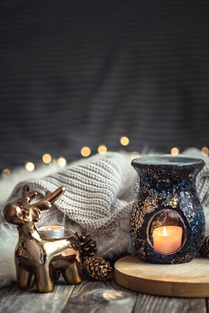 Christmas festive background with toy deer with a gift box, blurred background with golden lights and candles, festive background on wooden deck table