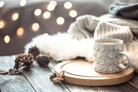 Coffee cup over Christmas lights bokeh in home on wooden table with sweater on a background and decorations. Winter mood, holiday decoration, magic Christmas. Stock fotó