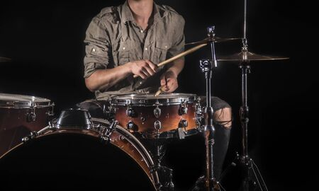 Professional drummer playing on drum set on stage on the black background with drum sticks and vintage look. Top view. Smoke effect Foto de archivo