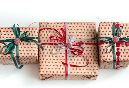 Christmas composition of various gift boxes wrapped in craft paper and decorated with satin red and green ribbons. Top view, flat lay. White background.