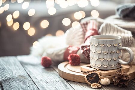 Coffee cup over Christmas lights bokeh in home on wooden table with sweater on a background and decorations. Winter mood, holiday decoration, magic Christmas. 免版税图像