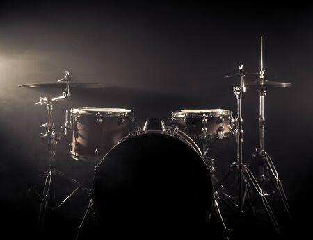 Drumstel Op Een Podium Op Een Donkere Achtergrond. Muzikaal drumstel op het podium. Vintage look met rookeffect