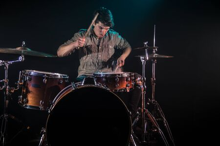 musician playing drums with splashes, black background with beautiful soft light, emotional play, music concept