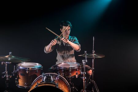 musician playing drums, black background and beautiful soft light, emotional play, music concept
