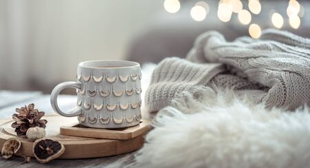 Coffee cup over Christmas lights bokeh in home on wooden table with sweater on a background and decorations. Winter mood, holiday decoration, magic Christmas. Foto de archivo