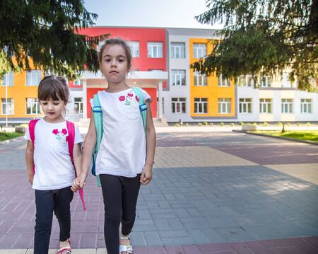 Back to school education concept with girl kids, elementary students, carrying backpacks going to class on school first day holding hand in hand together walking up building stair happily