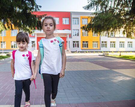Terug naar school onderwijsconcept met meisjeskinderen, elementaire studenten, met rugzakken die op de eerste schooldag naar de klas gaan en hand in hand samen gelukkig de bouwtrap oplopen