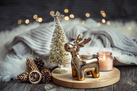 Christmas festive background with toy deer, golden lights and candles, wooden deck table and winter sweater Stock Photo