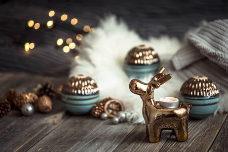 Christmas festive background with toy deer with a gift box, blurred background with golden lights, festive background on wooden deck table