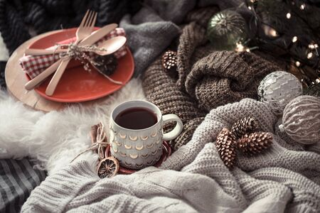 Cozy winter morning with cup of tea in bed. Steaming cup of hot coffee, tea standing near window. Christmas concept. Pillows, pine cones, gypsophila and fir tree branch on wool plaid.