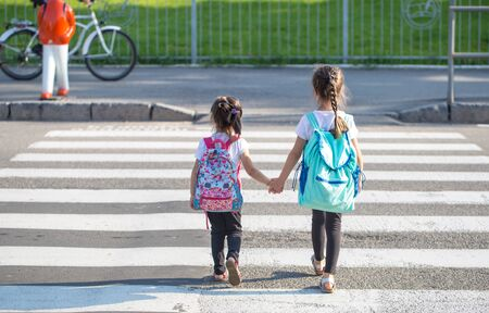 Back to school education concept with girl kids, elementary students, carrying backpacks going to class on school first day holding hand in hand together walking up building stair happily Banque d'images