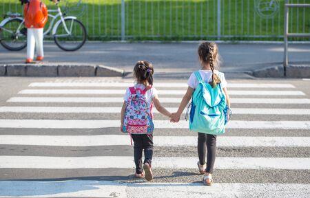 Concept d'éducation de retour à l'école avec des filles, des élèves du primaire, portant des sacs à dos pour aller en classe le premier jour de l'école, main dans la main ensemble en montant l'escalier du bâtiment avec bonheur Banque d'images