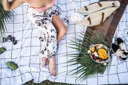 Picnic estivo, una ragazza con un piatto di frutta su un tappetino bianco. Il concetto di feste estive, cibo e svago. La vista dall'alto .
