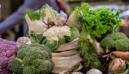 Display of fresh ripe organic broccoli, salad with greens and vegetables in cotton bag at the weekend farmers market with blurred background