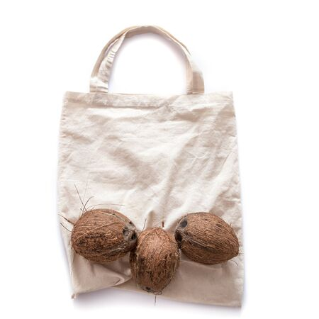 Zero waste and plastic free concept. Coconut on eco bag over white background. Flat lay. Copy space