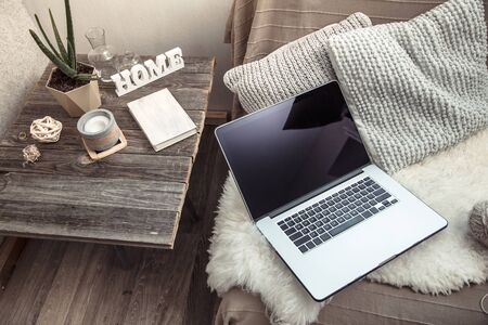 work at home with a computer on the couch .Home interior in a working atmosphere. Coziness and comfort. Stock Photo