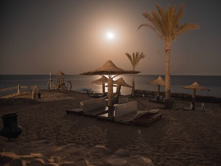Empty beautiful beach with umbrellas and sunbeds in Egypt . the concept of travel and recreation .Night snapshot. Stock Photo