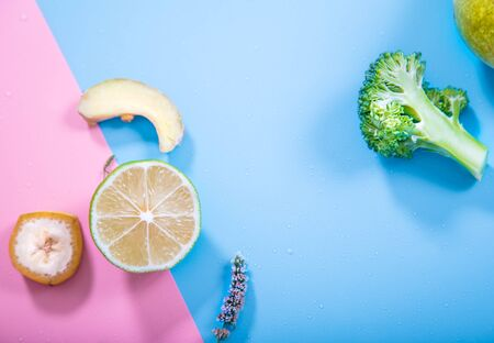Different fruits and vegetables on a colored background. Flat-lay. The view from the top. Stock Photo