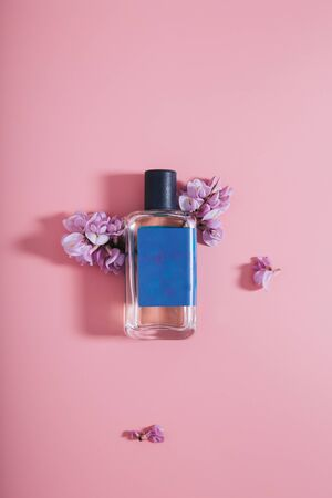 Bottle of parfumes on pink background with purple flowers
