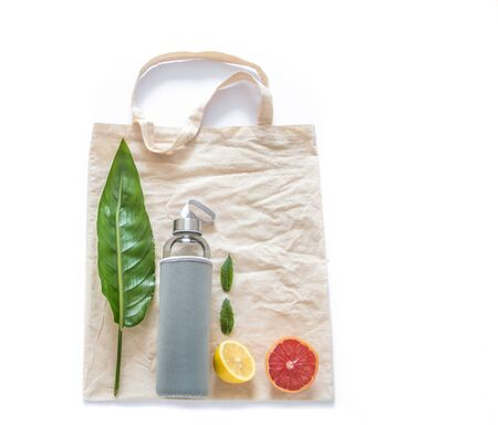 Cotton cloth tote bag with with water bottle groceries fruits raw lemons green leaf on white background trendy flat lay. Zero waste reusable eco friendly materials plastic free.