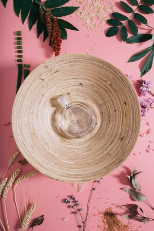 Creative flat lay top view of emptybamboo bowl with perfume on pastel millennial pink paper background copy space. Minimal writing concept template for text lettering blogging.
